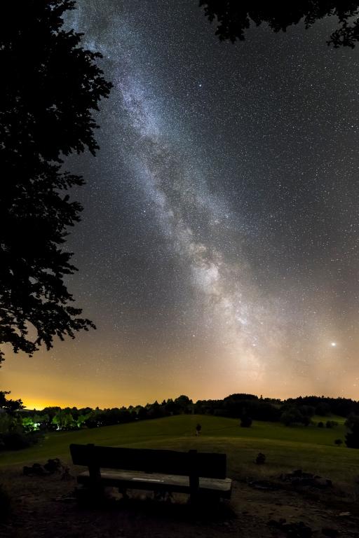 Jiří Hudec - Tour Nr. 21 - Lavička do vesmíru Lavička při turistické trase u skály Drátník vybízející k posezení a kochání se nočním pohledem na Mléčnou dráhu.